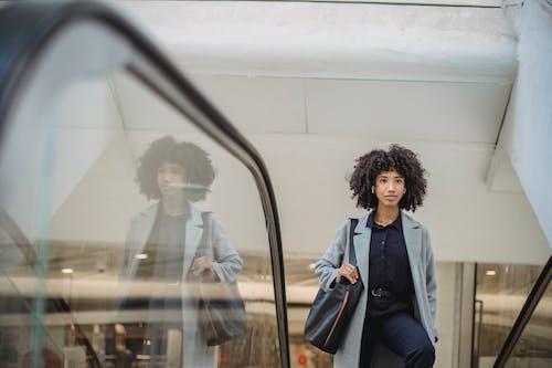 Black woman standing on escalator in mall