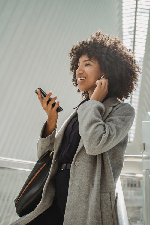 Side view of happy African American female in stylish outfit standing on stairs in modern building and holding mobile phone while listening to music in wireless earphones
