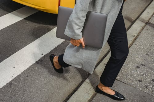 Crop anonymous female in casual outfit holding netbook while crossing asphalt road in city