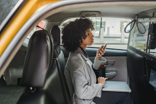 Side view of African American businesswoman in casual clothes holding mobile phone and laptop on knees while sitting in cab