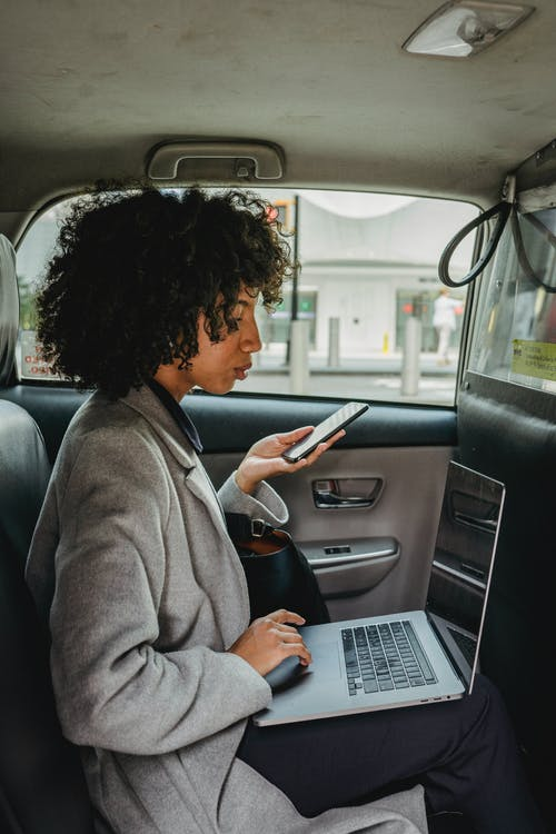 Side view of African American female freelancer browsing netbook while working on backseat of taxi