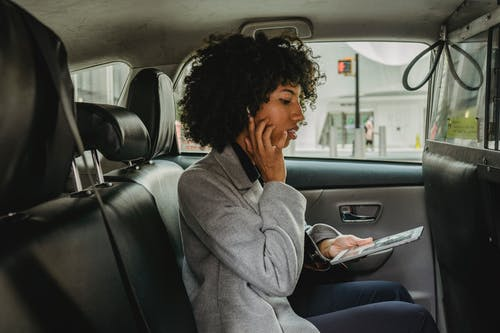 Businesswoman with wireless earphones and tablet on backseat