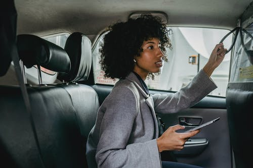 Side view of African American female with Afro hairstyle sitting on passenger seats of cab and holding mobile phone