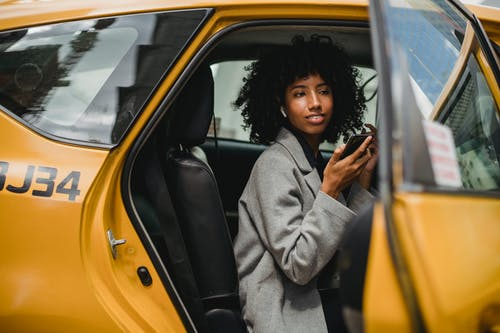 Black woman getting out of taxi on street