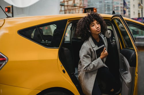 Woman in Gray Coat Standing Beside Yellow Car