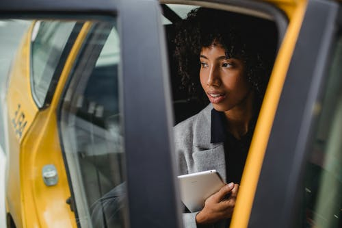 Expressive African American female holding tablet while sitting on passenger seat of yellow taxi and looking away