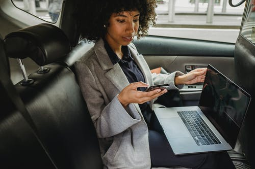 Crop African American female in formal clothes sitting with laptop on knees and browsing mobile phone in comfortable automobile