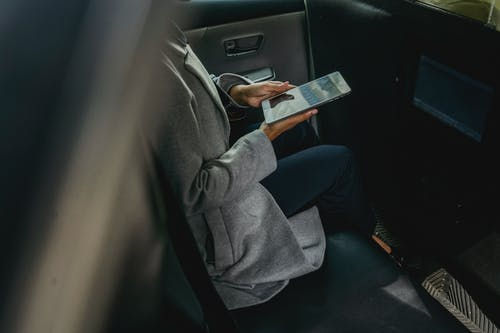 Crop unrecognizable female in casual clothes browsing tablet in backseat of modern cab