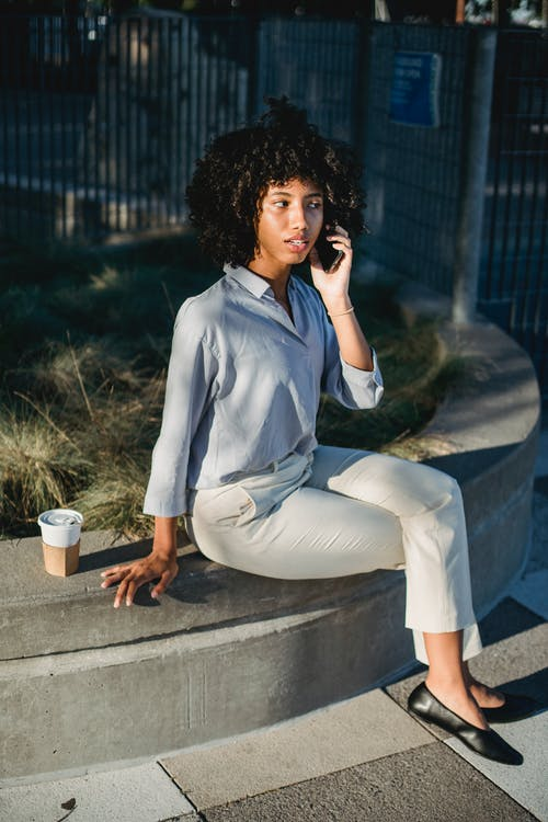 Full body of African American female in formal clothes sitting on stone border with crossed legs and talking on mobile phone during coffee break