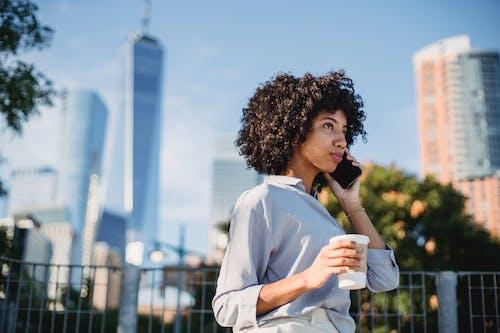 Black woman with coffee having phone call