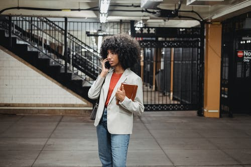 A Woman in a White Blazer Using a Mobile Phone