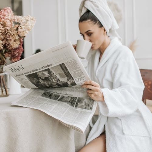 Woman in White Robe Reading Newspaper