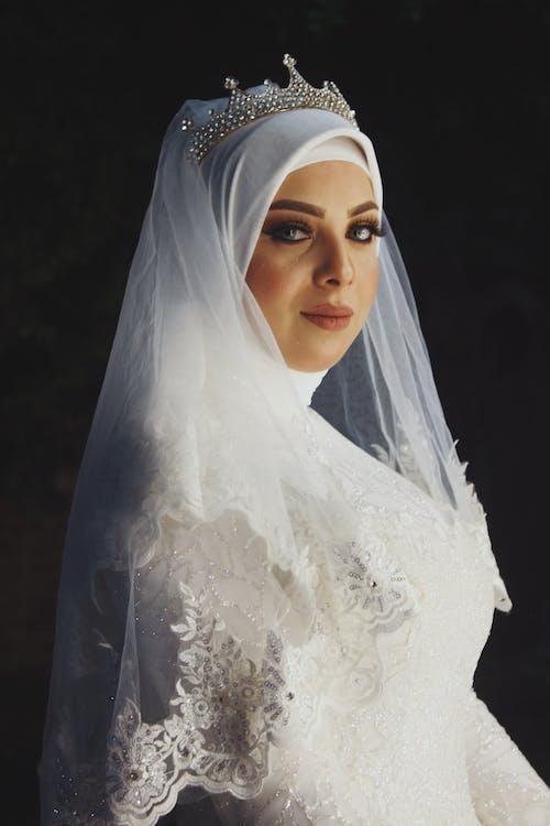 Elegant Muslim bride in hijab and veil standing in studio