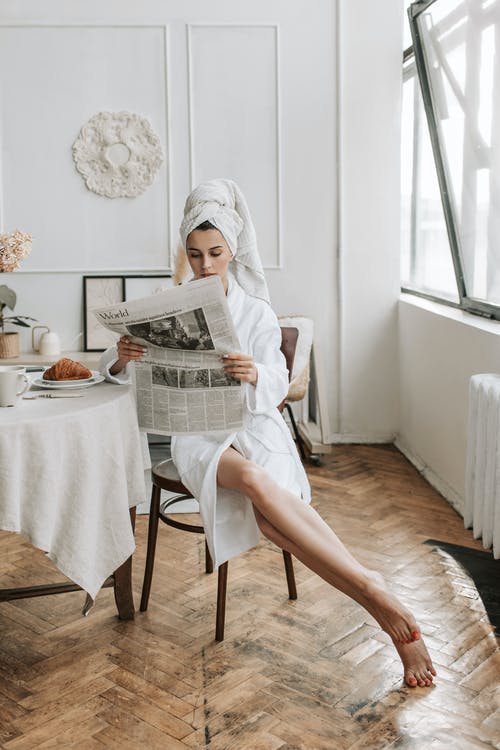 Woman in White Hijab Reading Newspaper