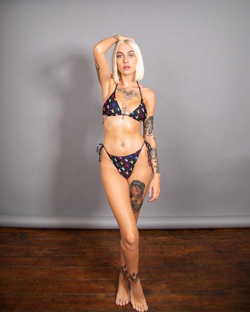 Woman in Black and White Polka Dot Bikini Standing on Brown Wooden Floor