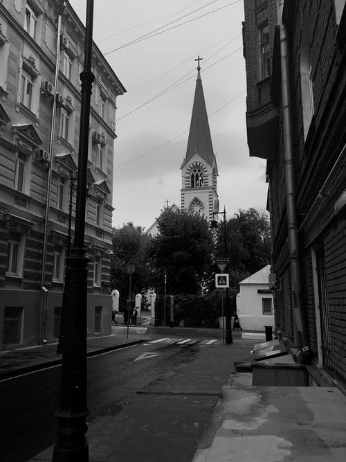 Historical cathedral and aged building on city street against overcast sky