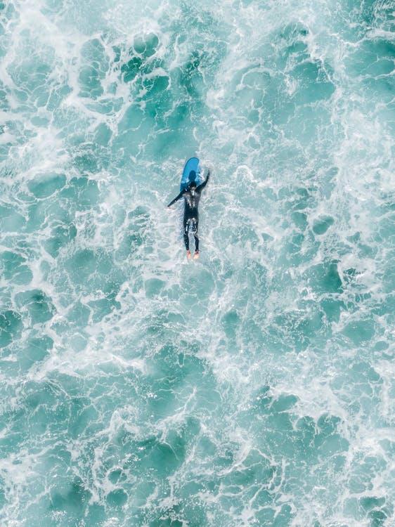 Faceless surfer in wavy ocean