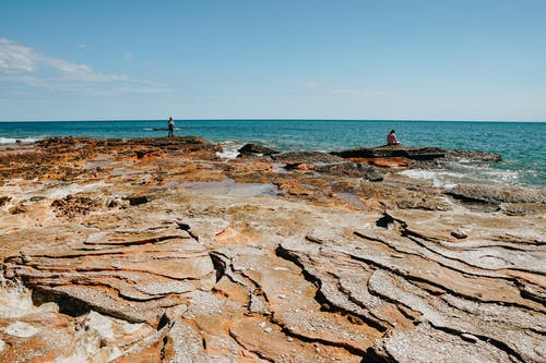 Light blue sky over natural bare brown stone slabs on rocky shore of endless silent sea