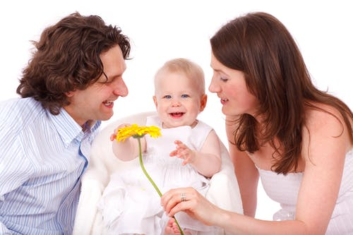 Man in White and Gray Stripe Button Up Long Sleeve Shirt Facing Baby in White Sleeveless Dress Beside Woman in White Strapless Dress Holding Yellow Flower