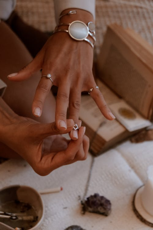 Person Wearing Silver Ring With White Manicure