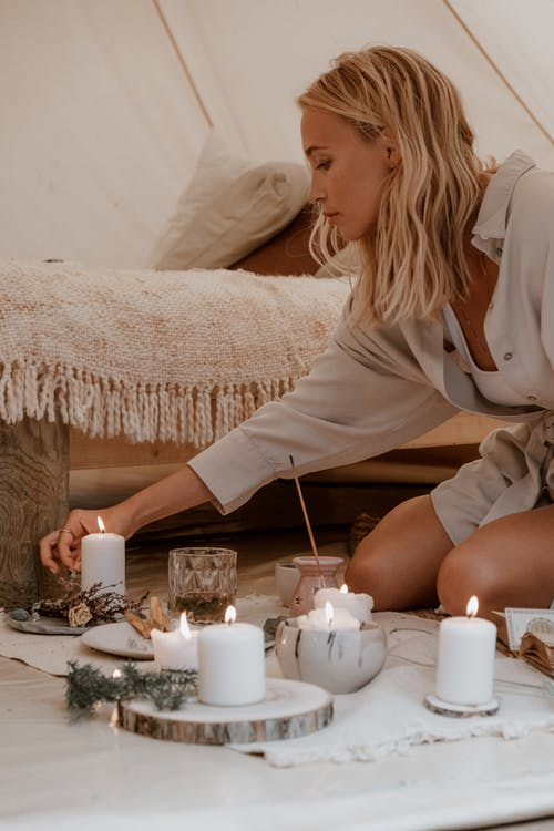 A Woman Lighting Candles on the Floor