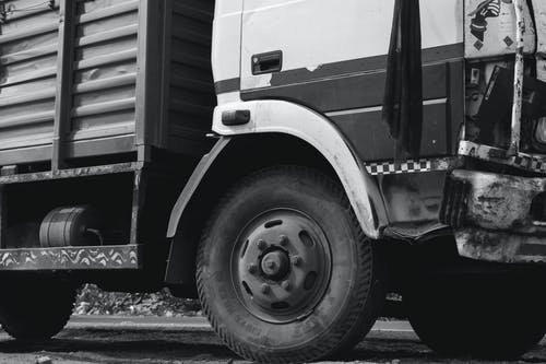 Grayscale Photo of Truck Wheel