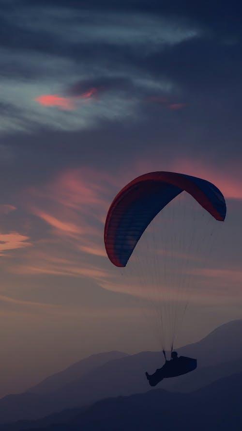 Man paragliding in dawn sky
