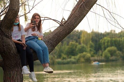 Woman in Blue Denim Jeans Sitting on Tree Branch