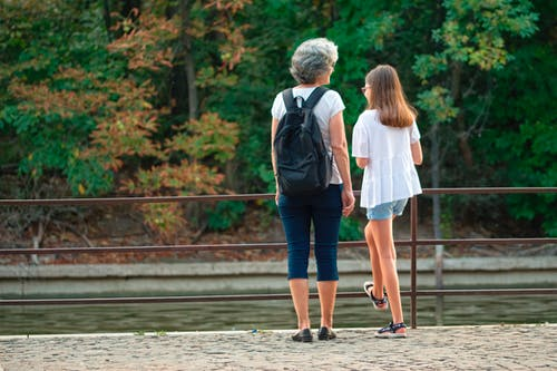 Man and Woman Walking on Wooden Dock