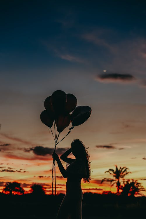 Silhouette of Woman Holding Balloons during Sunset
