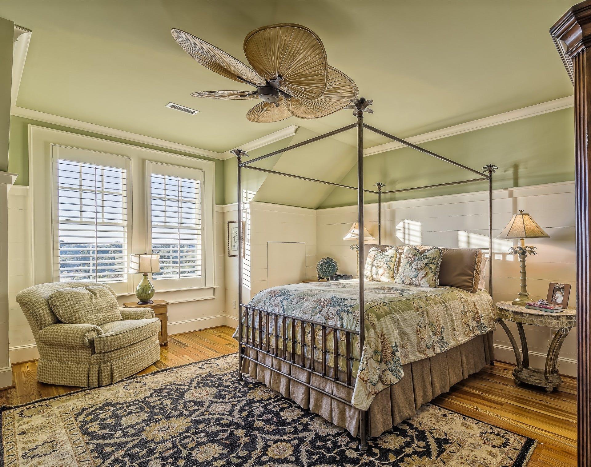Необычный дизайн интерьера с уникальной люстрой и высокой кроватью с балдахином.