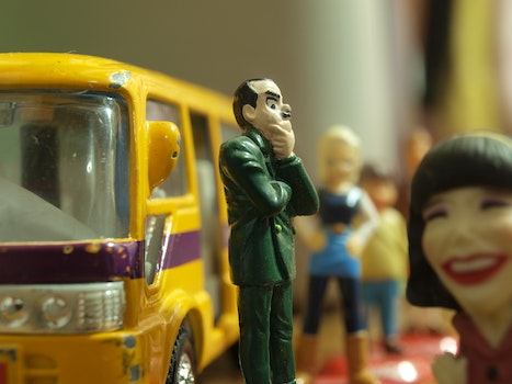 Man in Green Coat Figure Standing in Front of Yellow Toy Bus