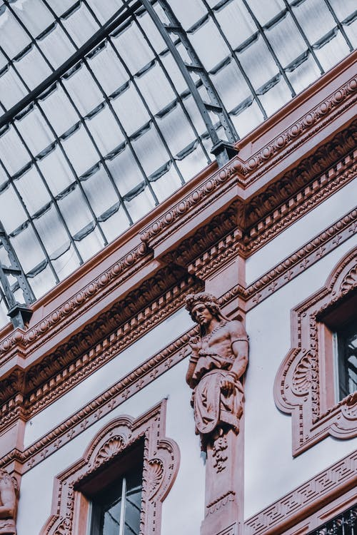 From below of sculptures and bas reliefs on walls of aged passage with glass roof located in Odessa