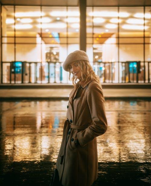 Woman in Brown Coat Standing on Wet Road