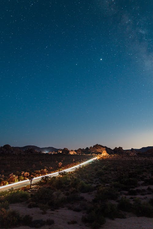 Road in the Middle of the Mountains during Night Time