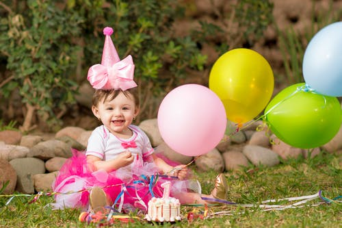Beautiful Baby Girl in Pink Birthday Hat Holding Balloons