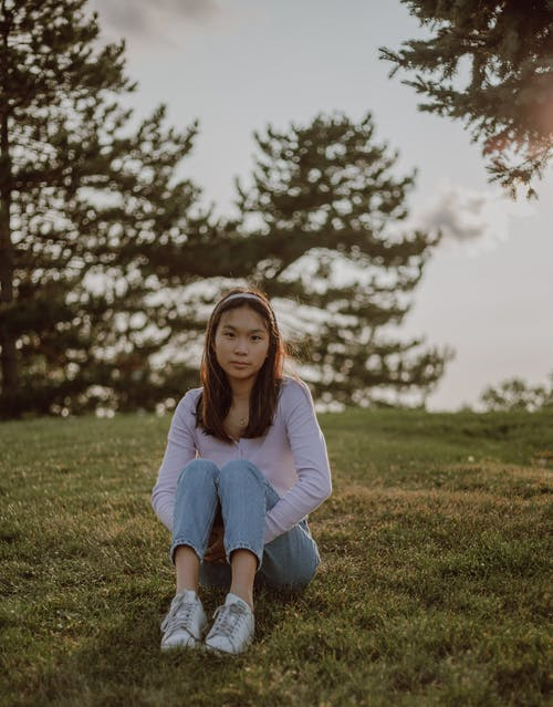 Calm ethnic woman sitting on green meadow