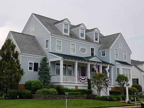 Blue and Gray Wooden House with Flags