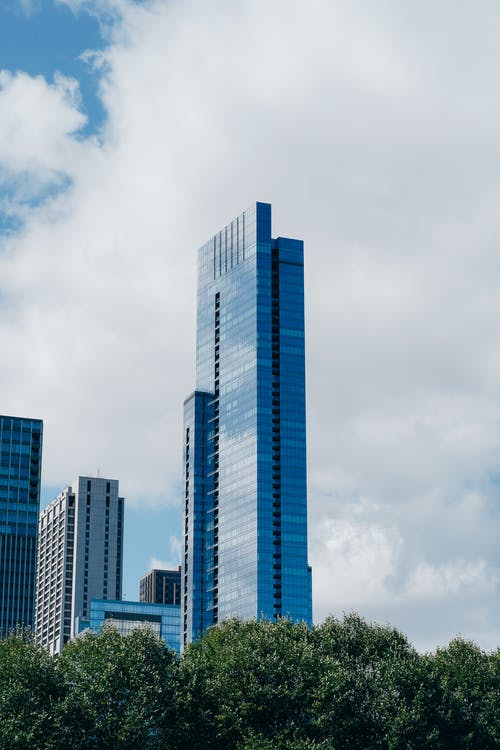Blue and White High Rise Building Under White Clouds