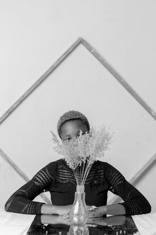 Black and white of unrecognizable young African American female in elegant dress resting at table with bunch of delicate flowers in vase against wall with geometric decor