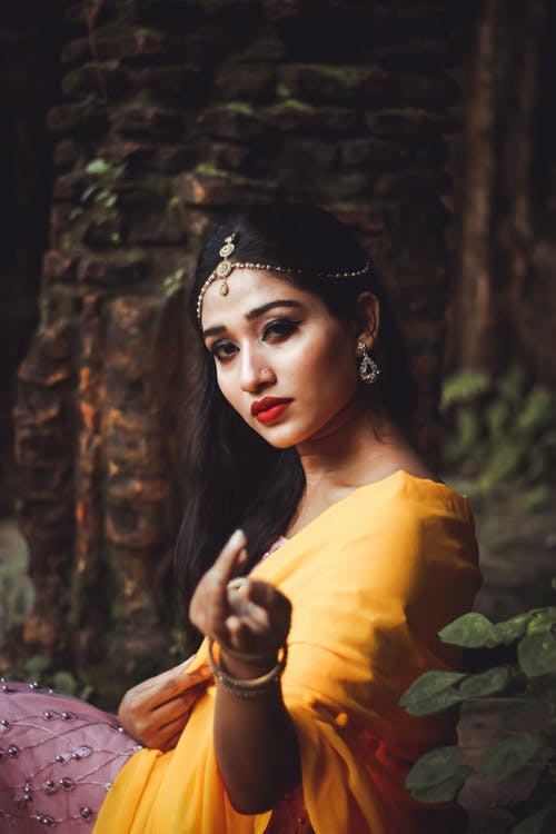 Pensive Indian woman in traditional garment by brick wall in park