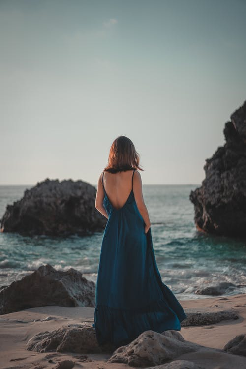 Nicht Erkennbare Weibliche Frau Im Maxikleid, Die Auf Felsiger Küste Steht
