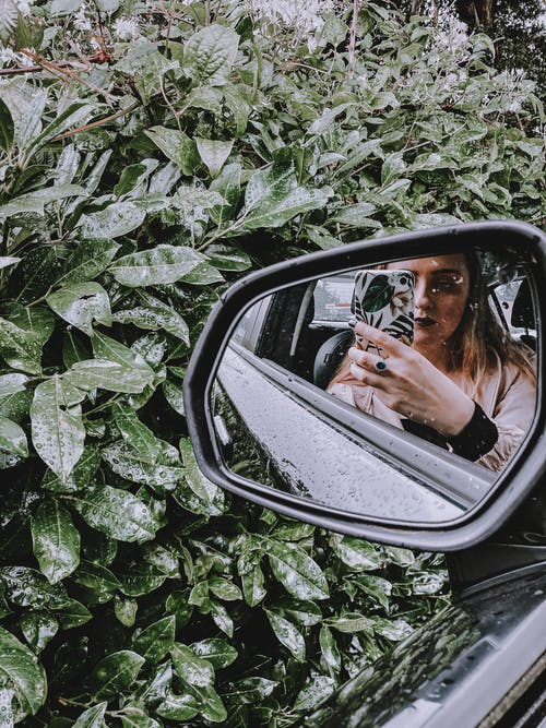 Young woman taking photo in mirror of car