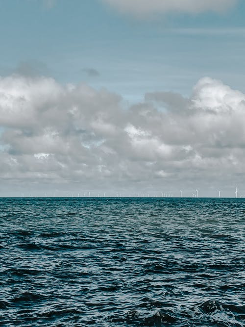 Vast waters of rippling endless ocean under sky with fluffy gray clouds in horizon