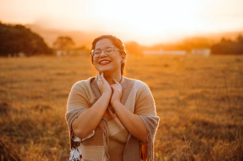 Happy young ethnic woman smiling with closed eyes in field at sundown