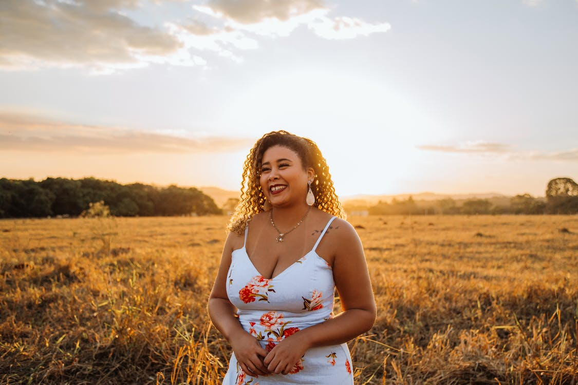 Happy ethnic woman smiling while standing in field at sunset
