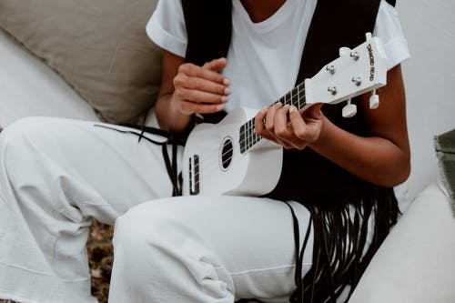 Person in White T-shirt Playing White Electric Guitar