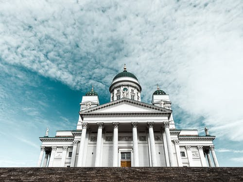 Majestic white cathedral with domes and pillars against blue sky