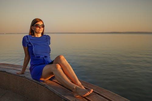Woman in Blue Dress Sitting on Dock