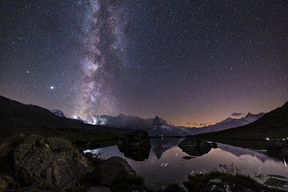 Body of Water Near Mountain Under Starry Night